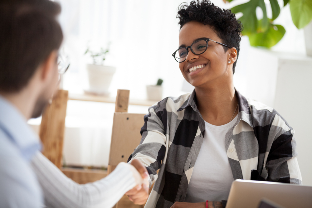 Smiling aspiring intern shaking hands in a job interview
