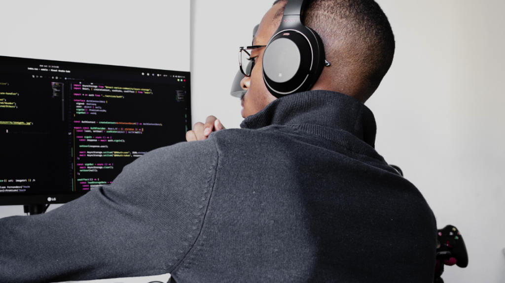 Image of a developer at his desk with code on his computer and headphones on.