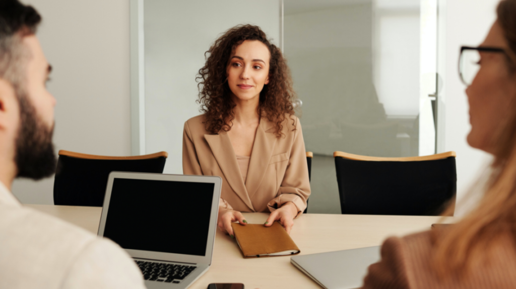 Candidate being interviewed by two recruiters at a desk by Edmond Dantès from Pexels
