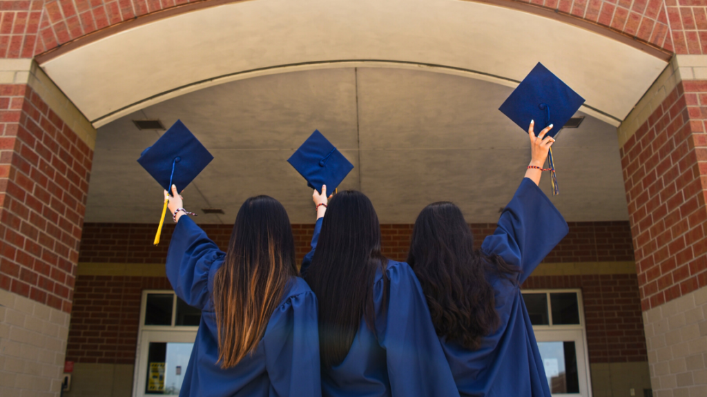 Three 2021 graduates in their gowns holding up their caps