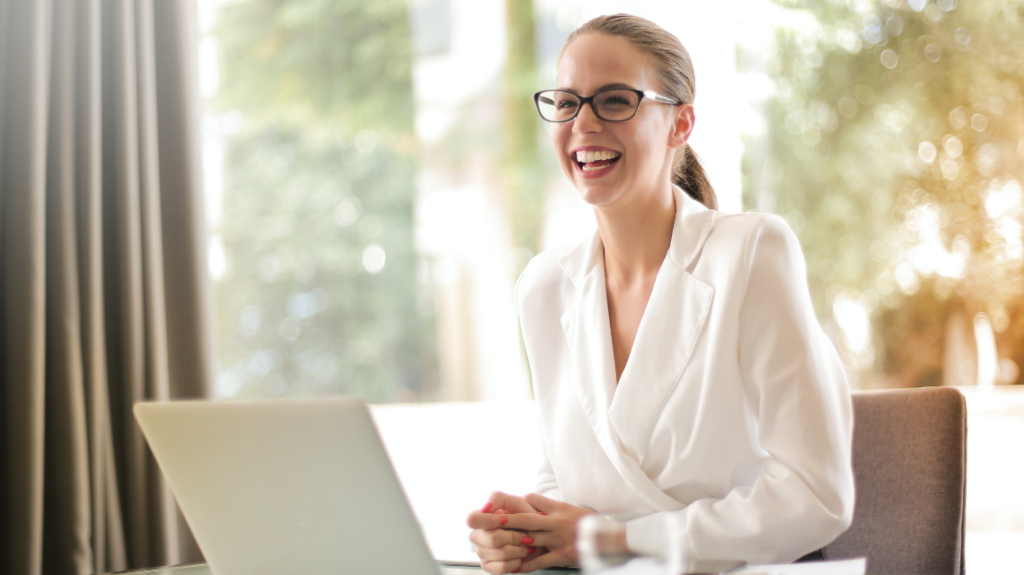 Entry-level employee at work laughing in front of her laptop.