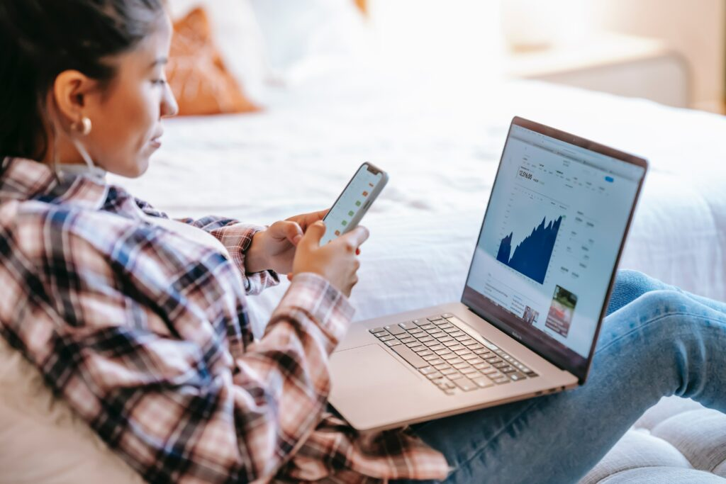 Data Analyst using her phone and laptop to read charts