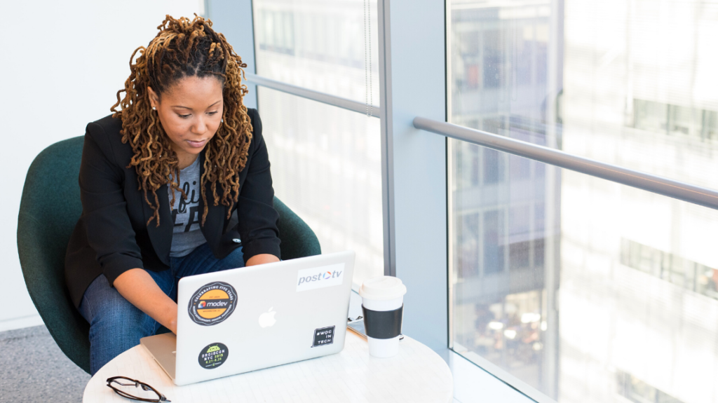 Woman in business casual wear sitting at a table working on her laptop in a corporate office