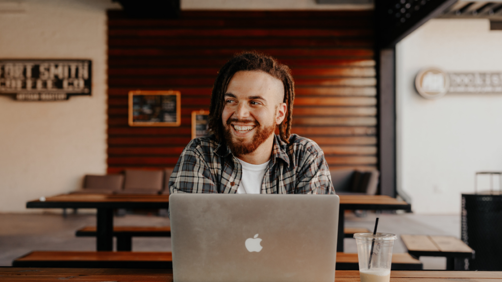 happy man finishing work early, sitting outside with a laptop and a vanilla milkshake, after implementing a 5-hour workday. photo by brooke cagle from unsplash