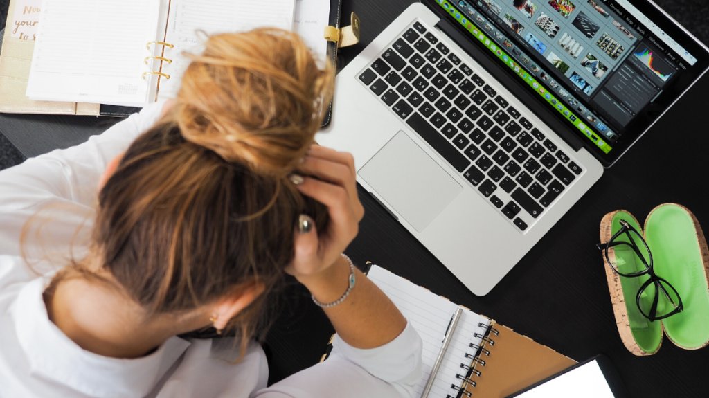 woman stressed out at her work desk after having too much work to complete in a 5-hour workday. photo by energpiccom from pexels