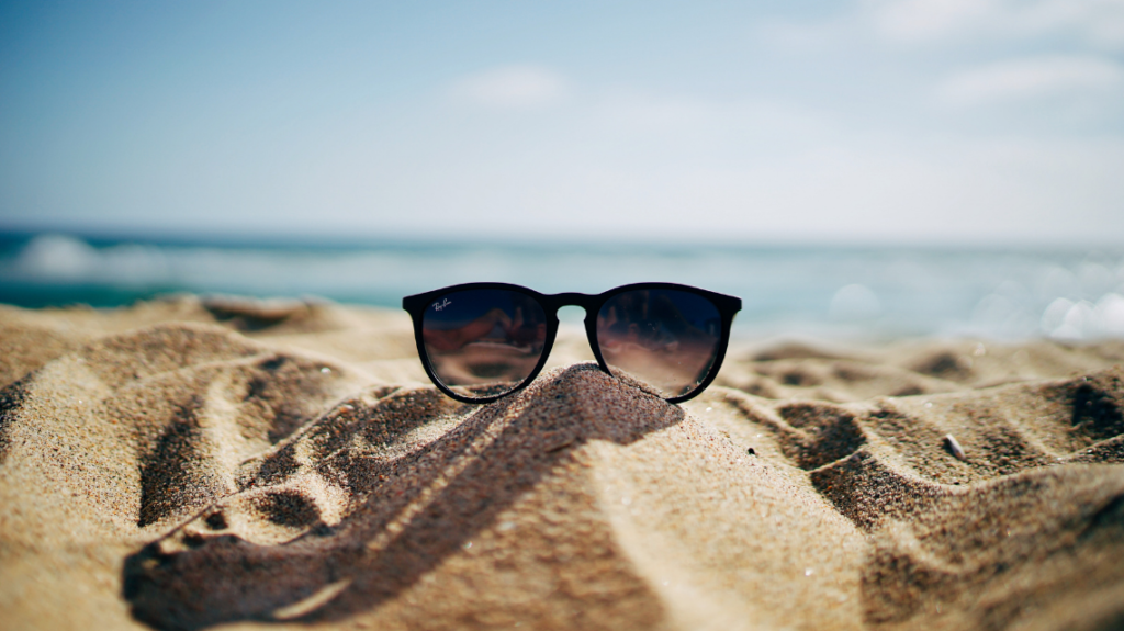 black sunglasses on a sandy beach, symbolising an employee enjoying the sun after being granted the best PTO policies at work. photo by ethan robertson from unsplash.