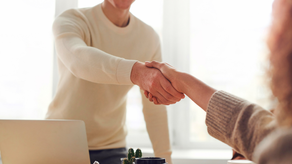 two people shaking hands at brilliant interview after sending out an inclusive job description. photo by fauxels from pexels