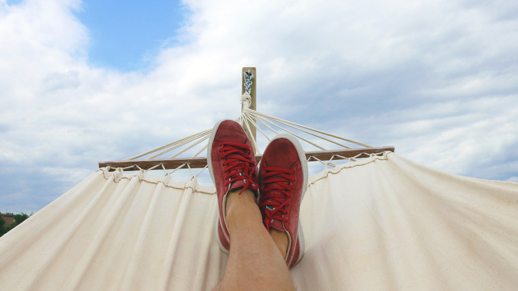 person on a hammock resting with their feet up during their vacation after implementing the best holiday policies. photo by mateusz dach from pexels