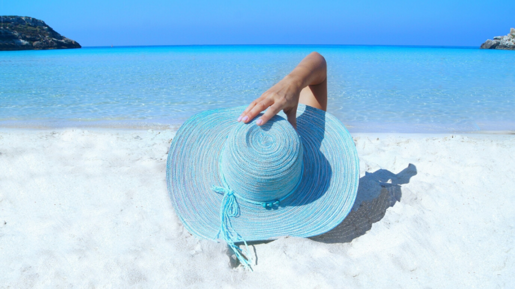 woman lying on a sunny white sandy beach with a bright blue hat and deep blue sea in the background, after her work employed the best holiday policies. photo by pixabay from pexels