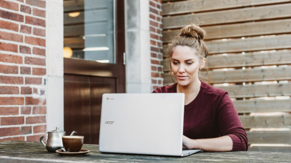 Woman at outside bench on her laptop reading an accessible job description