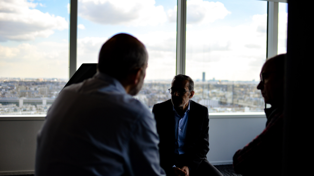 Four business people in an office, negotiating a deal.