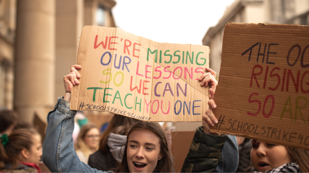 Gen Z girls at a protest for climate change. Sign reads: we're missing our lessons so we can teach you one.