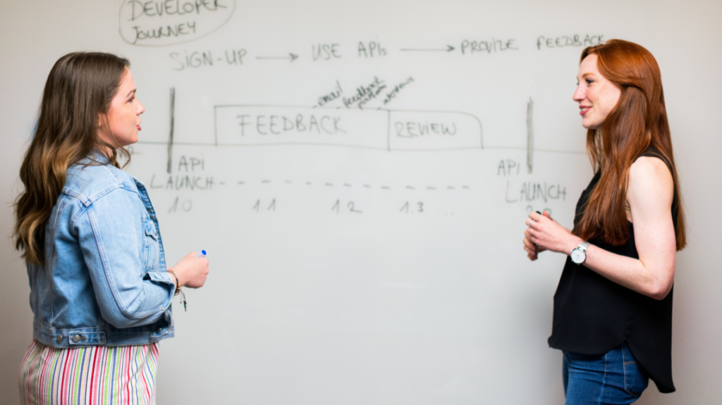 Two young professional women talking in front of a busy whiteboard