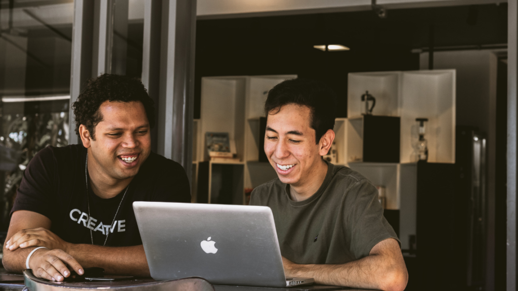 Two professional men smiling while working on a laptop.
