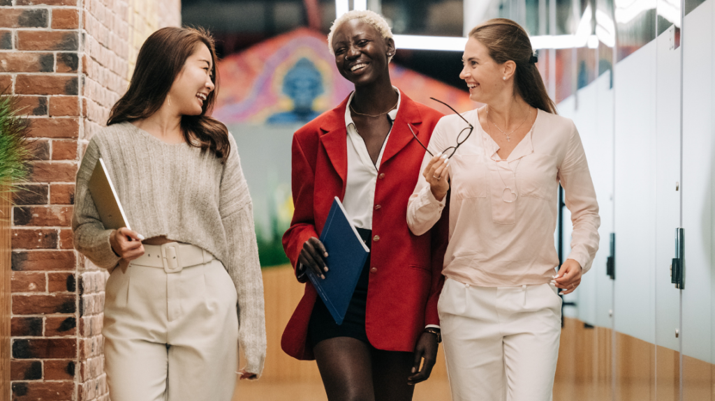 Three young diverse professional women walking through an office.