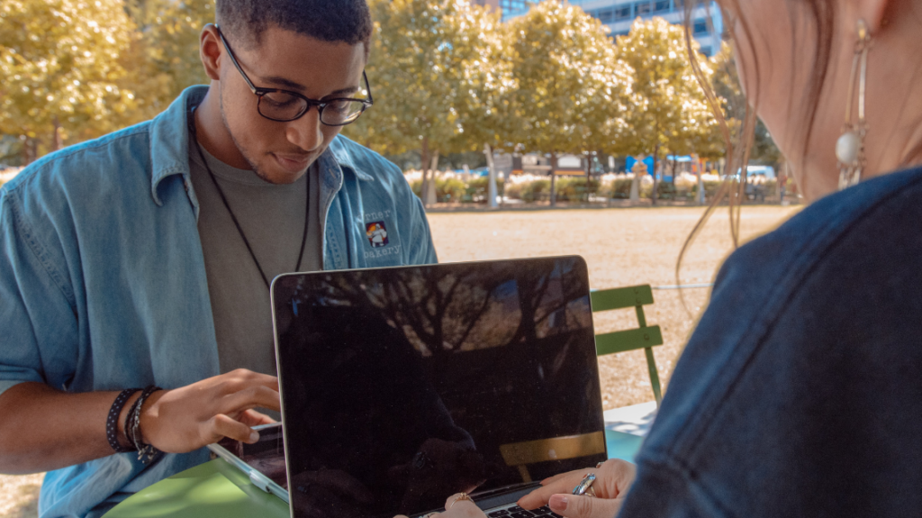 Two young Gen Z employees on their laptops outside the office.